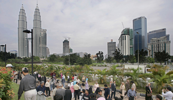 Tourists from around the world crowd at the city center park in front of Malaysian landmark Petronas Twin Tower (L) in downtown Kuala Lumpur, 04 January 2007.  Tourism remains one of the important industries for the country.  Year Visit Malaysia 2007, is targeting 20.1 million tourists and over RM44 billion (12.6 billion USD) in revenue. This makes tourism the second largest foreign exchange earning industry. AFP PHOTO/TEH ENG KOON